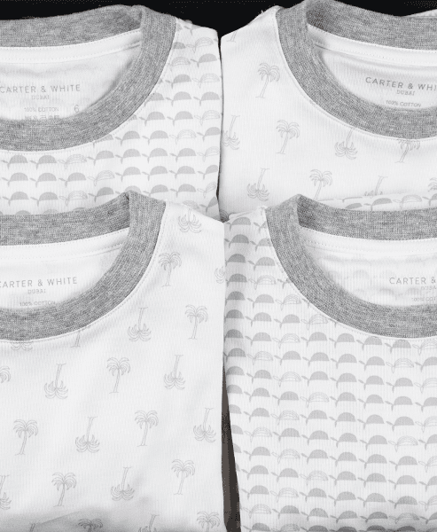 4 pajamas for kids in palm and whale print with gray trim in a gift box